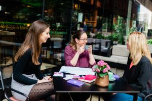 Three women around a table having coffee